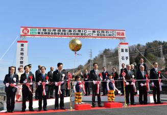 テープカットで釜石道が全線開通を祝う国や自治体の関係者=9日、釜石市甲子町
