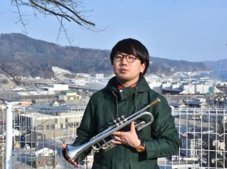 復興が進む町を眺め「将来は大槌にジャズバーをつくりたい」と語る台隆裕さん=大槌町小鎚