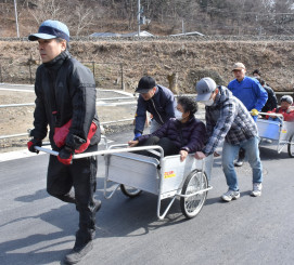 要援護者をリヤカーに乗せ、協力して避難する住民
