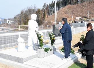 高台に建立された地蔵に手を合わせ震災犠牲者を悼む住民