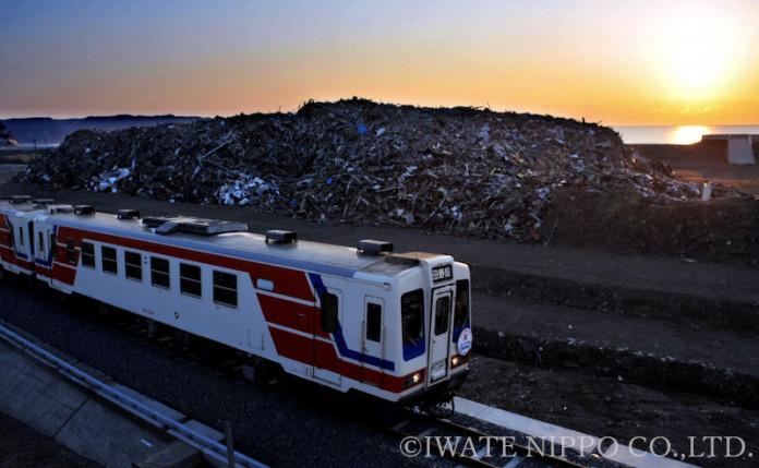 【希望の明日】田野畑-陸中野田(24・3キロ)で運行を再開した三陸鉄道北リアス線。久慈駅発の一番列車ががれきの山の端から顔を出した朝日を浴びて田野畑駅を目指した。約1年ぶりの復活は地元住民に勇気と希望を与え、鉄道関係者らは全線開通の誓いをあらたにした=2012年4月1日、野田村野田