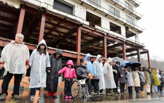 冷たい雨の中、たろう観光ホテルの前で手をつなぎ、海に向け黙とうする住民ら=11日午後2時46分、宮古市田老