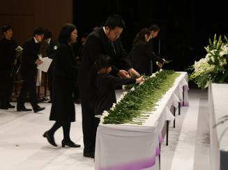 犠牲者の冥福を祈り、花を手向ける参列者=11日午後4時5分、久慈市・アンバーホール