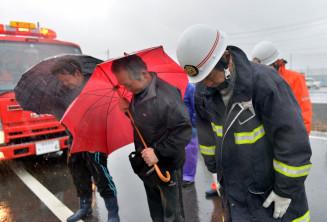嵐の中で、殉職した3人に祈りをささげる(右から)内舘実さん、白野博さん、白野悟さん=11日午後2時46分、山田町境田町