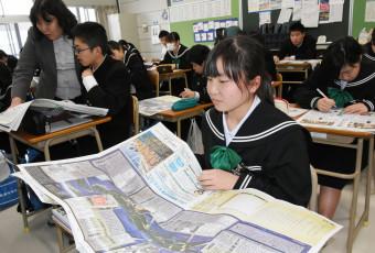 岩手日報社の東日本大震災8年の特別号外を開く真備中の2年生