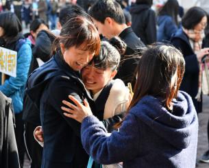 自分の受験番号を見つけ、家族と抱き合って喜ぶ受験生=14日、盛岡市津志田・盛岡四高