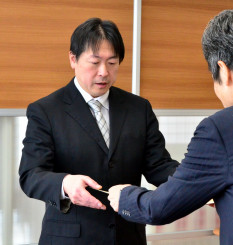 佐々木哲総括課長から表彰状を受ける笠井成人社長(左)