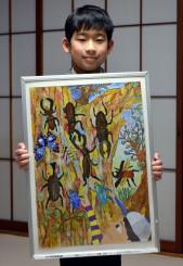 大好きな虫たちを生き生きと描いた作品を手に受賞を喜ぶ手島大和君