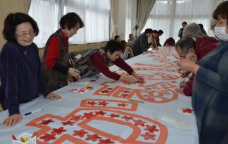 メッセージを書いたシールを貼り付けて横断幕を製作する参加者
