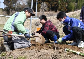 笑顔で会話を楽しみながら苗に土をかける参加者ら