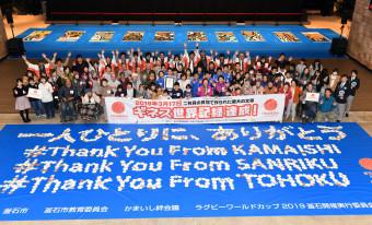 「サンキュー・フロム・カマイシ」。1012枚の貝殻でメッセージを作り、ギネス世界記録の達成を喜ぶ市民ら=17日、釜石市大町・釜石市民ホール