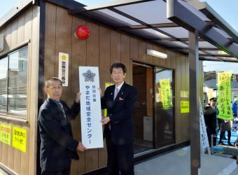 看板を設置する佐藤信逸町長(右)と伊藤進一会長