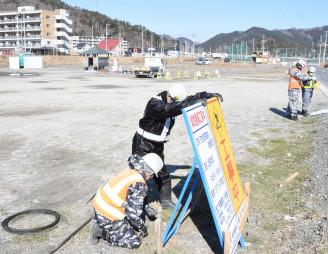 町が解体した旧役場庁舎跡地に緑地整備工事の看板を設置する作業員