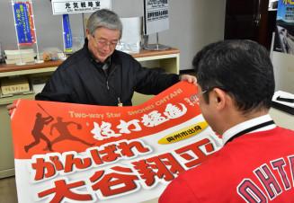 早速応援サポーターに登録し、ポスターを受け取る高橋勉さん(左)