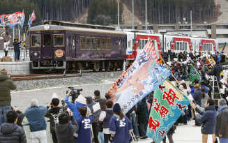 大漁旗を手にした人たちに迎えられ、鵜住居駅に到着した三陸鉄道リアス線の記念列車=23日午前、釜石市