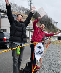 横断幕を掲げ、小旗を振って記念列車を歓迎する西野泰輔運転士(左)と柴田征志運転士=23日、宮古市・三陸鉄道磯鶏駅