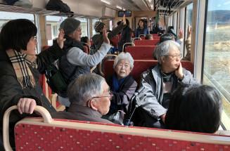 にぎわう三鉄車内から、沿線で歓迎する住民らに手を振って応える乗客=24日、大槌町内