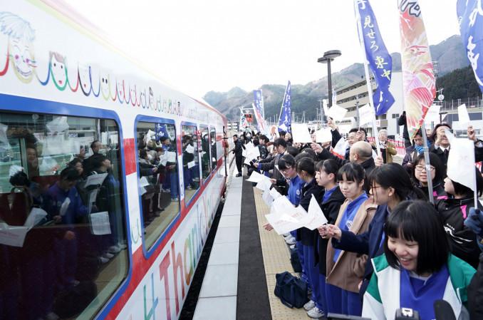 釜石東中の生徒が描いた「笑顔」がつながったデザインの「三陸鉄道スマイル列車」を出迎える同校の生徒ら。車体には16カ国語の言葉で「ありがとう」の文字も刻まれている