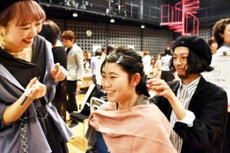現役美容師からヘアアレンジしてもらう加藤華菜さん(中央)