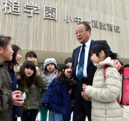 大槌学園の児童に囲まれ、笑顔を見せる伊藤正治教育長。「大槌町の未来を担う人材に育ってほしい」と願いながら30日に退任する=25日、大槌町大槌