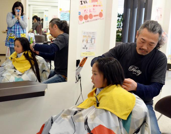 母美穂さんが見守る中、ヘアドネーションに協力するため髪を切る和田起太朗ちゃん(手前)
