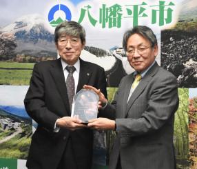 寺本樹生事務局長から「地域発!いいもの」への選定を示す盾を受け取る岡田久副市長(左)