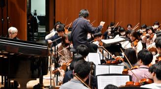 本番を想定し、監督の坂本龍一さん(左)と演奏する団員ら