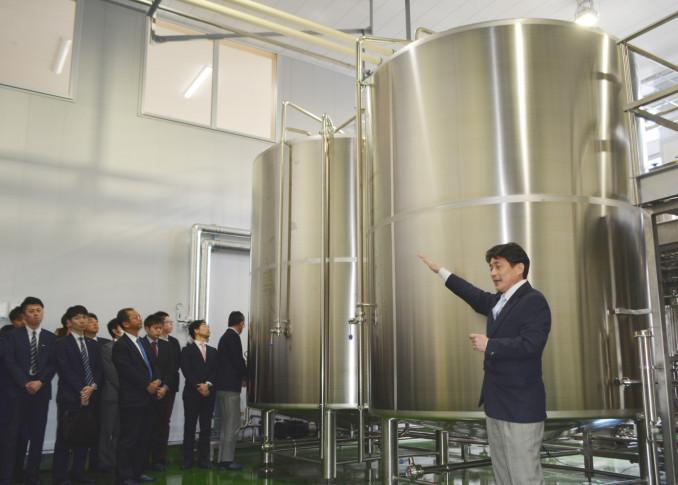 雫石工場の設備を来場者に説明する木村剛社長(右)