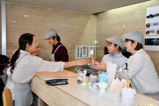 カウンターで勤務する斉藤麻衣さん(右から2人目)らスタッフ