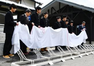 塗装し新品同様になった自転車スタンドを披露する宮古工高の生徒ら