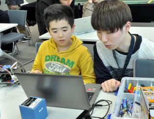 受講生にプログラミングについてアドバイスする田尻隼人さん(右)