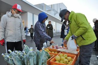 新鮮な野菜や果物の販売を通じ交流する生産者と買い物客