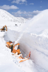 青空の下、路面の雪を吹き飛ばすロータリー除雪車=8日、八幡平市・八幡平アスピーテライン