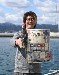 海中で熟成させた酒のボトルとマイカルテを手に「陸前高田の魅力を現地で知って」とPRする佐々木学さん
