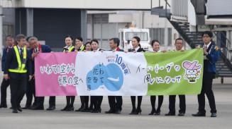 ビル開業10周年を祝う横断幕で、出発客を見送る県空港ターミナルビル職員ら