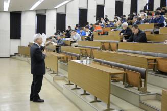 岡田秀二学長(左)の講義を受ける学生や市民