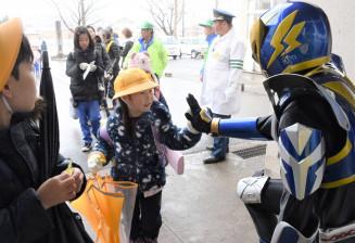ハチマンタイラー(右)とハイタッチを交わし、交通安全を誓う平舘小の児童