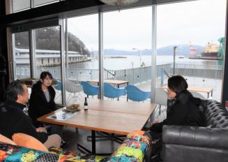 開放的な店内で釜石港の景色を楽しむ参加者。13日にオープンし、釜石や三陸の魅力を発信する=11日、釜石市魚河岸