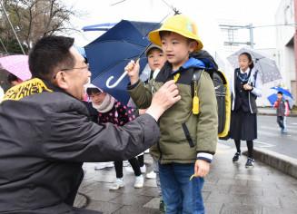藤原淳市長(左)に黄色い羽根を貼り付けてもらう児童