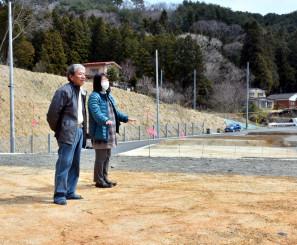 引き渡しを受けた防集の宅地に立つ岩間幸雄さん(左)と黒沢由美子さん=大槌町赤浜
