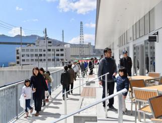 晴天の下、オープンしたばかりの魚河岸テラスの雰囲気を楽しむ来場者=13日、釜石市魚河岸