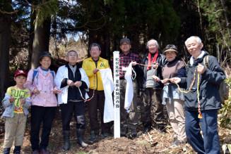 登山道の入り口に新たに設置した標柱を除幕する一関市室根町と気仙沼市唐桑町の関係者