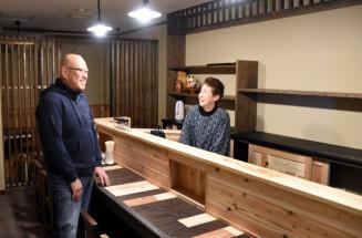 釜石市大町の新店舗で、再開を喜ぶ常連客に笑顔を見せる菊池悠子さん(右)