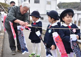 ロープにこいのぼりをくくり付ける園児たち