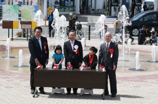 噴水のスタートボタンを押す関係者。4~11月に久慈駅前を彩る