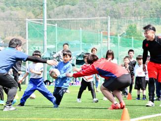 大人と一緒にラグビーを楽しむ子どもたち