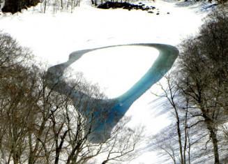 雪解けに伴いドーナツ状に水面が現れた石沼