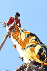 高さ約16メートルのはしごで虎舞を披露する住民