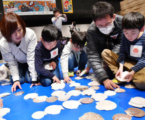下書きが隠れるように、丁寧にホタテ貝を並べる参加者