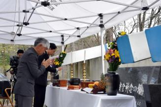 解体される航空安全祈念の塔に、犠牲者の供養と無事故を願い手を合わせる参列者